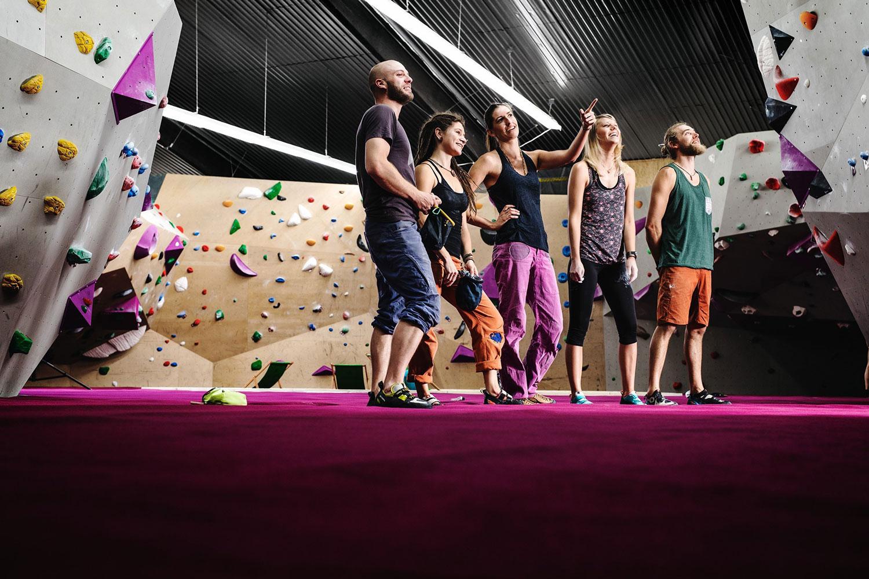 Fünf Personen schauen auf eine Kletterwand