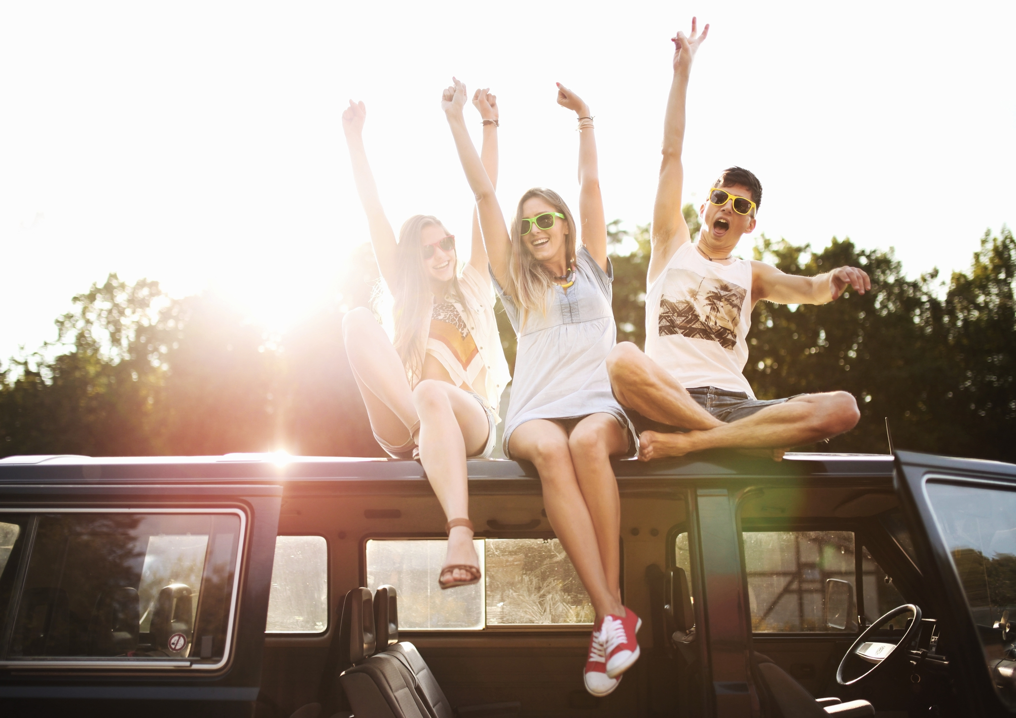 Drei Jugendliche mit Sonnenbrillen sitzen auf einem kleinen Bus und reißen jubelnd die Arme nach oben.