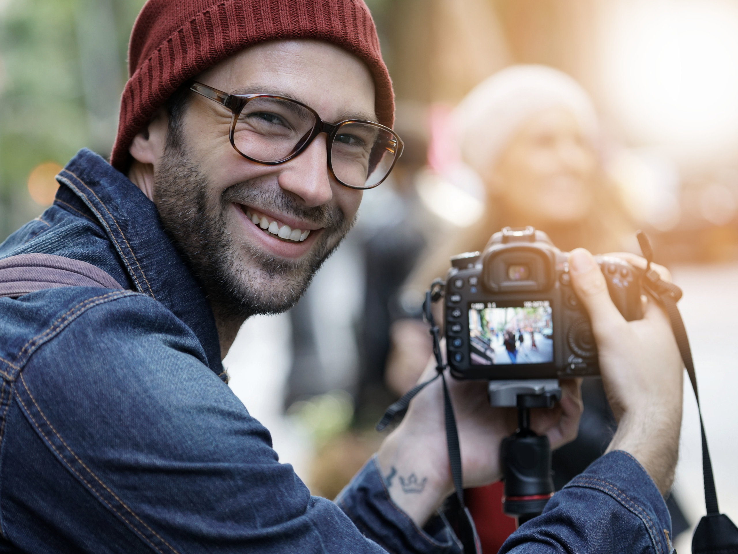 Ein Fotograf blickt in die Kamera während er ein weibliches Model fotografiert
